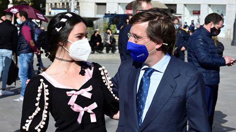 El alcalde de Madrid, José Luis Martínez Almeida saluda a una mujer vestida con el traje tradicional en la visita que realizó a la carpa informativa del PP instalada en la Puerta del Sol