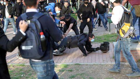 Un policía nacional por los suelos durante las cargas que se han registrado en protesta por el acto de precampaña de Vox