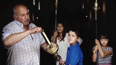 Lixandro Piñeiro con los niños Rosalía del Chano, Jaime de Manuela y María de Cachoupo, preparando la salida de la procesión de Las Veigas. Carolina del Chano saluda a Etelvina de Pontones, una de las mujeres que carga con la imagen de la Virgen de las Veigas