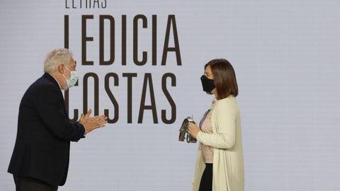 A escritora Ledicia Costas recibe o seu premio de mans do presidente do Parlamento galego, Miguel Santalices