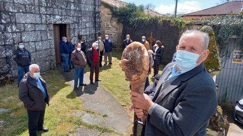 Momento no que José Manuel Mosquera ofrece un lacón na poxa antes da misa de San Wintila