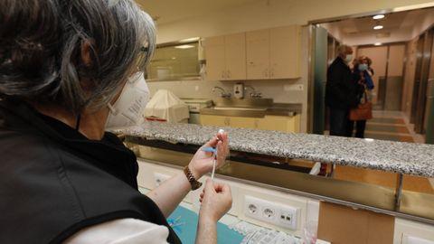 Vacunas como esta que preparan en el Hospital da Mariña están siendo administradas a la población de la comarca que le toca, lo que contribuye a mitigar el impacto de la pandemia