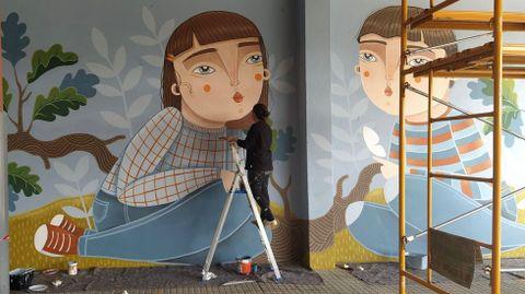 Abi Castillo creó dos grandes obras para el CEIP de Roxos con la ayuda de los alumnos de primaria. Los de infantil participaron también en el proceso con preguntas a la autora y dibujando en sus pizarrillas. La artista, más conocida por sus ilustraciones y trabajos en cerámica, lleva un par de años en el arte mural, un mundo que  le divierte mucho, dice. Este es su primer trabajo en la comarca de Santiago, aunque ya había hecho antes otras obras a gran escala para centros educativos de la zona de Vigo