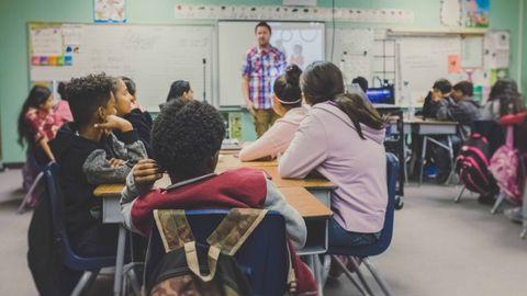 Niños atienden a la explicación de un profesor en el aula