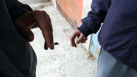 Unos jóvenes fumando porros a la salida de un instituto de Santiago