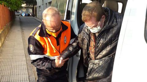 Un voluntario de Protección Civil ayuda a una vecina de A Rúa a bajar de la furgoneta en uno de los traslados
