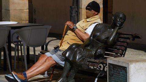Un hombre sentado al sol con su mascarilla en la Plaza del Fontán en Oviedo