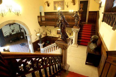 Escalera principal de entrada al pazo de Meirás llena de estatuas, adornos, cuadros y trofeos