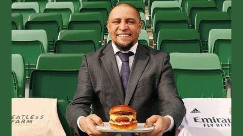 El exjugador del Real Madrid Roberto Carlos con una hamburguesa vegana
