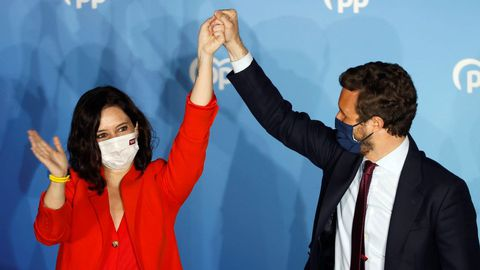 El líder del PP, Pablo Casado, alza el brazo de la candidata popular, Isabel Díaz Ayuso, tras confirmarse su victoria arrolladora en las elecciones de Madrid