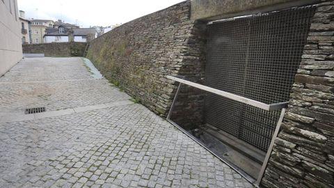 Rejilla de ventilación, sellados al fondo junto a la muralla y canalizaciones que provocan filtraciones en el yacimiento de la Domus do Mitreo