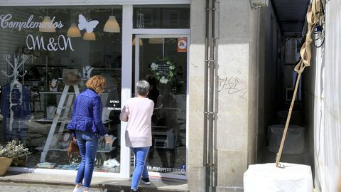 Dos mujeres entrando en uno de los locales afectados por la carpa, la cual tiene a menos de un metro de su fachada