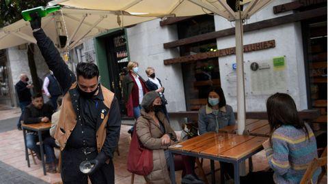 Un camarero escancia sidra en una terraza llena de gente en la Plaza del Fontán en Oviedo