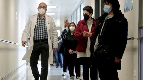 Un médico pasa junto a una fila de personas que esperan para vacunarse en el hospital de Monforte
