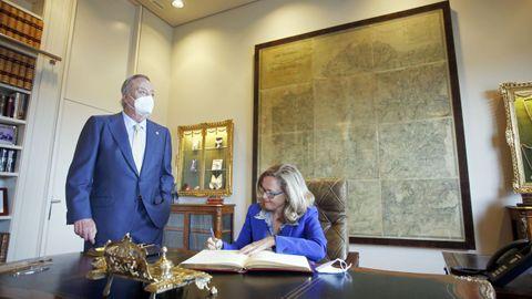 Nadia Calviño, firmando en el libro de honor, en presencia de Santiago Rey