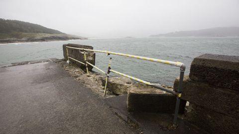 Balarés. Hace más de un año que el temporal destrozó parte del pretil del muelle y sigue con una valla provisional.
