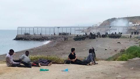 Un grupo de inmigrantes marroquí observa el despliegue del Ejército de Tierra