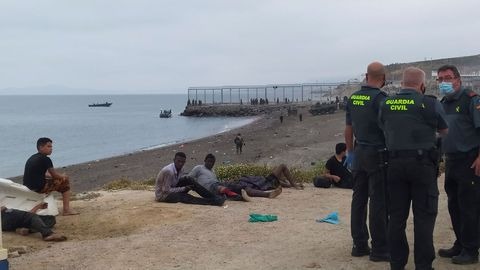 Miembros de la Guardia Civil conversan junto a un grupo de inmigrantes que han cruzado la frontera a nado por los espigones fronterizos de Ceuta