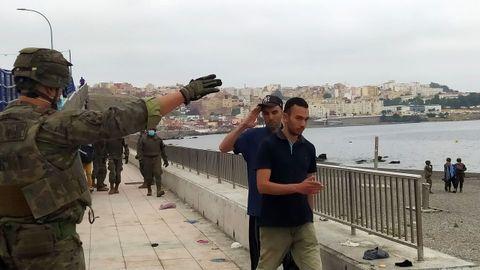 Un miembro del Ejército de Tierra da instrucciones a un grupo de inmigrantes