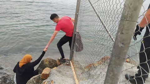 Dos inmigrantes escalan las rocas de uno de los espigones fronterizos de Ceuta