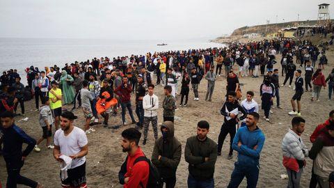 Cientos de personas esperan en la playa de la localidad de Fnideq (Castillejos), en Marruecos, para cruzar los espigones de Ceuta este martes en una avalancha de inmigrantes sin precedentes en España