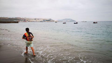 Un niño observa desde la playa de la localidad de Fnideq (Castillejos), en Marruecos, uno de los espigones de Ceuta