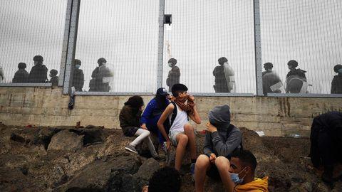 Miembros de la policía Nacional vigilan la verja que separa Ceuta de la localidad marroquí de Fnideq