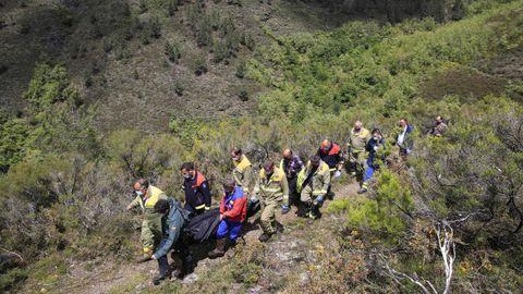 Bomberos forestales, miembros de Protección Civil y Guardia Civil trasladan el cuerpo del desaparecido en la aldea de Ventosa