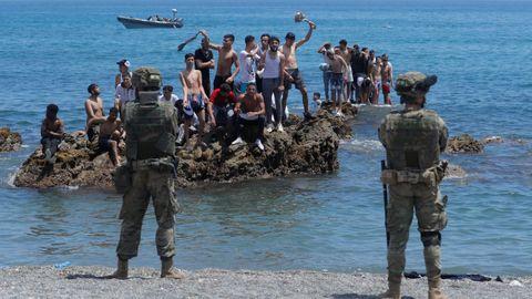 Marroquíes en las rocas del Tarajal, vigilados por soldados españoles