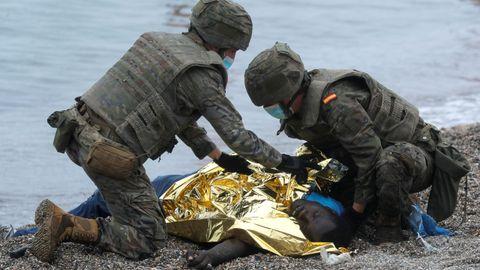 Soldados españoles auxilian a uno de los inmigrantes llegados a la playa del Tarajal