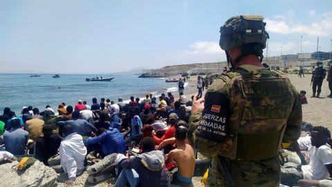 Un soldado vigila a un grupo de inmigrantes que lograron cruzar uno de los espigones fronterizos de Ceuta