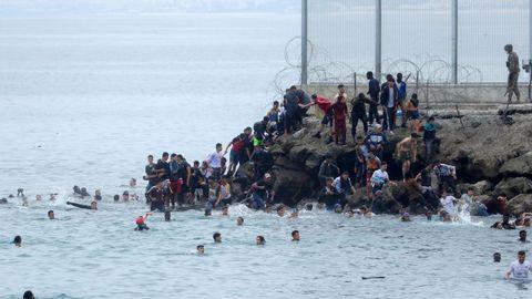 Ciudadanos marroquíes agolpados en uno de los espigones fronterizos de Ceuta