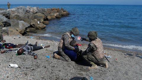 Dos soldados ayudan a uno de los inmigrantes que han llegado a la playa de El Tarajal