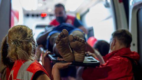 Efectivos de Cruz Roja atienden a un migrante con signos de hipotermia tras intentar cruzar a España por el agua en la playa de El Tarajal.