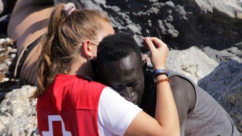 Una trabajadora de la Cruz Roja y un migrante que ha logrado cruzar uno de los espigones fronterizos de Ceuta este martes se abrazan