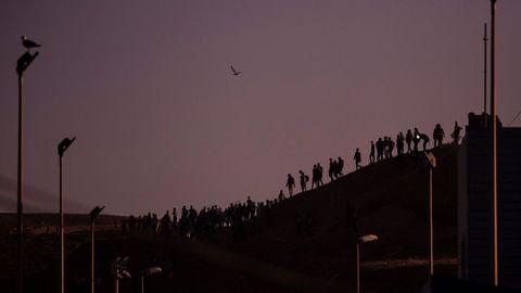 Varios migrantes esperan para tratar de cruzar la frontera de Marruecos en Ceuta