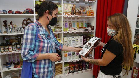 Una voluntaria de la tienda Comercio Xusto muestra uno de sus productos a una clienta