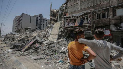 Dos jóvenes palestinos observan los daños producidos por bombardeos israelíes en Gaza