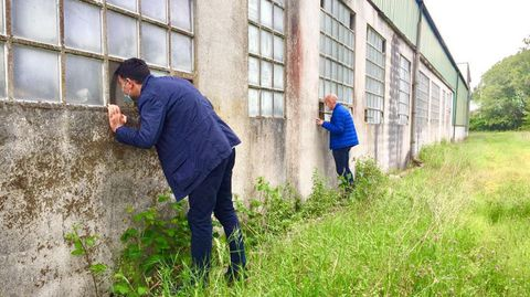El portavoz del PP, Javier Castiñeira, y el alcalde de Begonte, mirando las naves de Manuel Mallo
