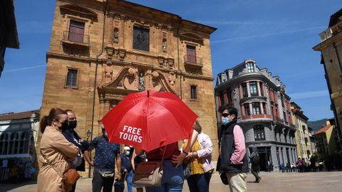 Un grupo de turistas atienden las explicaciones de un guía en la plaza del Ayuntamiento de Oviedo