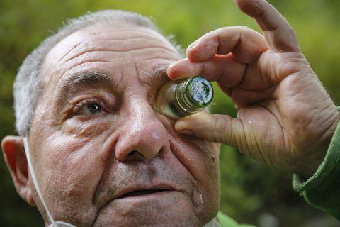 Un home que se operou dun ollo e acude diariamente a darlle auga termal para as curas. Nas ruinas do antigo Balneario das Caldas en Ourense,  baixo a ponte da estrada N-120. 29/05/2021
