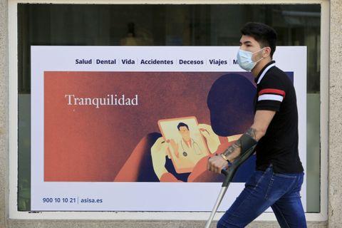 Ambiente no centro de Lugo o día previo a entrada en vigor das novas restricións polo coronavirus. Un xove pasa ó lado do cartel dunha aseguradora que ofrece  tranquilidade . 07/05/2021