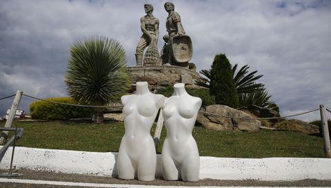 Dous manequíns da feira, pousados no chan diante da escultura á familia mariñeira na apertura da mobilidade en O Grove