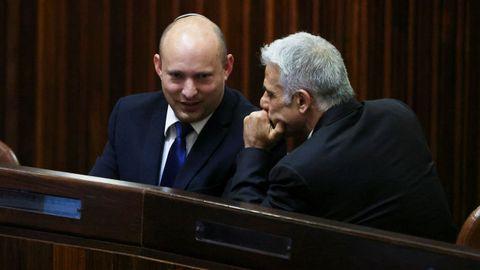 Bennett y Lapid conversan durante la sesión parlamentaria para elegir el nuevo presidente