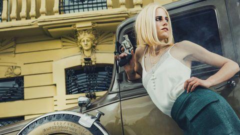TOP LENCERO Y FALDA RECTA: El diseñador gallego Jorge Vázquez firma esta falda recta con bolsillos plastón que luce Iria como una Bonnie muy actual. El top lencero de Mango es un acierto, al igual que todos los colgantes (en especial la cruz de perlas de la joyería Obradoiro) que destaca en este look. La media melena rubia, con raya al medio, de Iria apoya su caracterización como el icónico personaje de Faye Dunaway en su posado en Puerta Real en A Coruña.