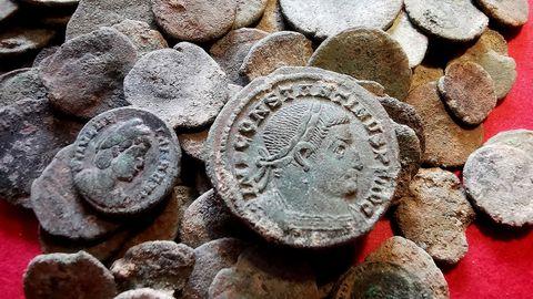 Algunas de las monedas encontradas en la cueva de Berció (Grado, Asturias) de la época romana. En primer plano, una efigie del emperador Constantino