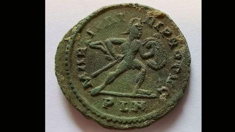 Una de las monedas encontradas en la cueva de Berció (Grado, Asturias) de la época romana