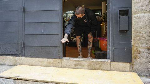 José María Marcos, propietario de un negocio de tatuajes, muestra hasta dónde llegó el nivel del agua con las lluvias