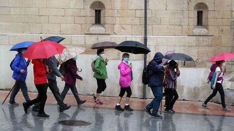 Un grupo de peregrinos se protegen de la lluvia con paraguas