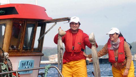 Dos turistas durante una jornada de pesca a bordo de un barco de pesca en O Grove.